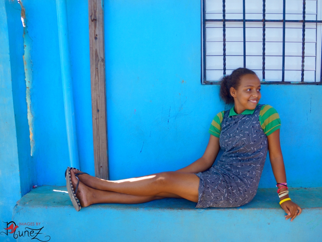 Girl Sitting with Blue Background